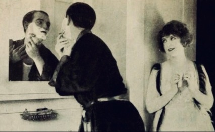 Couple. Man shaving as woman watches. May Allison pub. photo of home life for Photoplay 1922 (USPD artist life, pub.date/Commons.wikimedia.org)