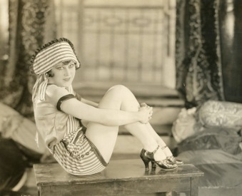 Woman sitting on table. Cecille Evans. 1925 publicity photo. (USPD. pub.date, Artist life/Commons.wikimedia.org)