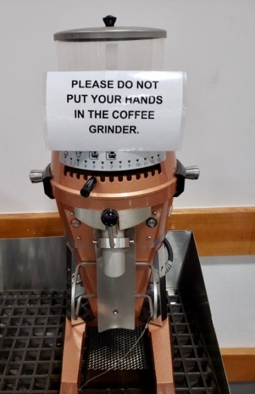 Store's Coffee bean grinder with odd sign on it. (© image. copyrighted, all rights reserved. No permissions granted)
