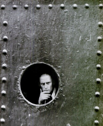 Man peering out ship portal. 1940. German prisoner on Candian prison ship.(USPD. pub.date, artist life)
