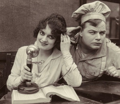 "1916 couple using phone (from 1916 film, ""The Waiters' Ball"". Keystone Film Co./USPD.pub.date, artist life, publicity still/Commons.wikimedia.org)"