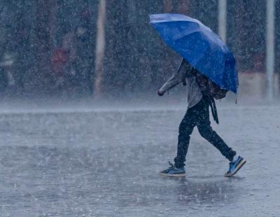 MAn walking in rain under umbrella (Emmanuelkwizera/Commons.wikimedia.org)