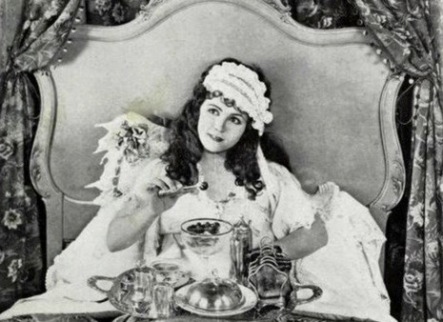 vintage woman in bed with mask and breakfast in bed (1922 Cover of Universal Weekly with Gladys Walton (USPD.pub.date, artist life/Commons.wikimedia.org)
